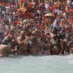 Sadhus, or Hindu holy men, take a dip in the Ganges river during