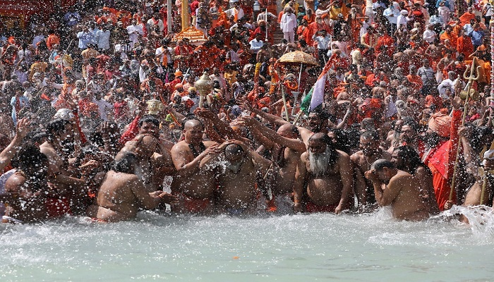 Sadhus, or Hindu holy men, take a dip in the Ganges river during